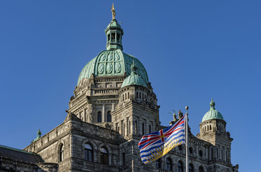 British Columbia Parliament Building BC Flag Victoria BC Canada on a against a blue sky